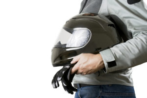 Torso of a motorcyclist in protective gear holding a helmet and gloves. Isolated on white background
