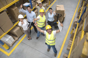 Workers at a warehouse with thumbs up