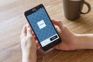 man hand holding screen shot of Uber application